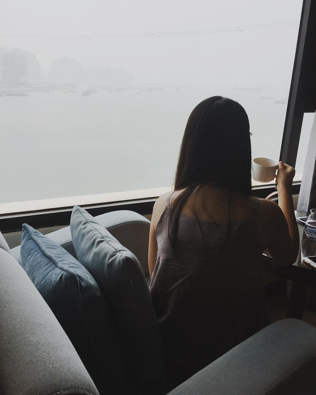 Thu Ha enjoying her drink by the club lounge window